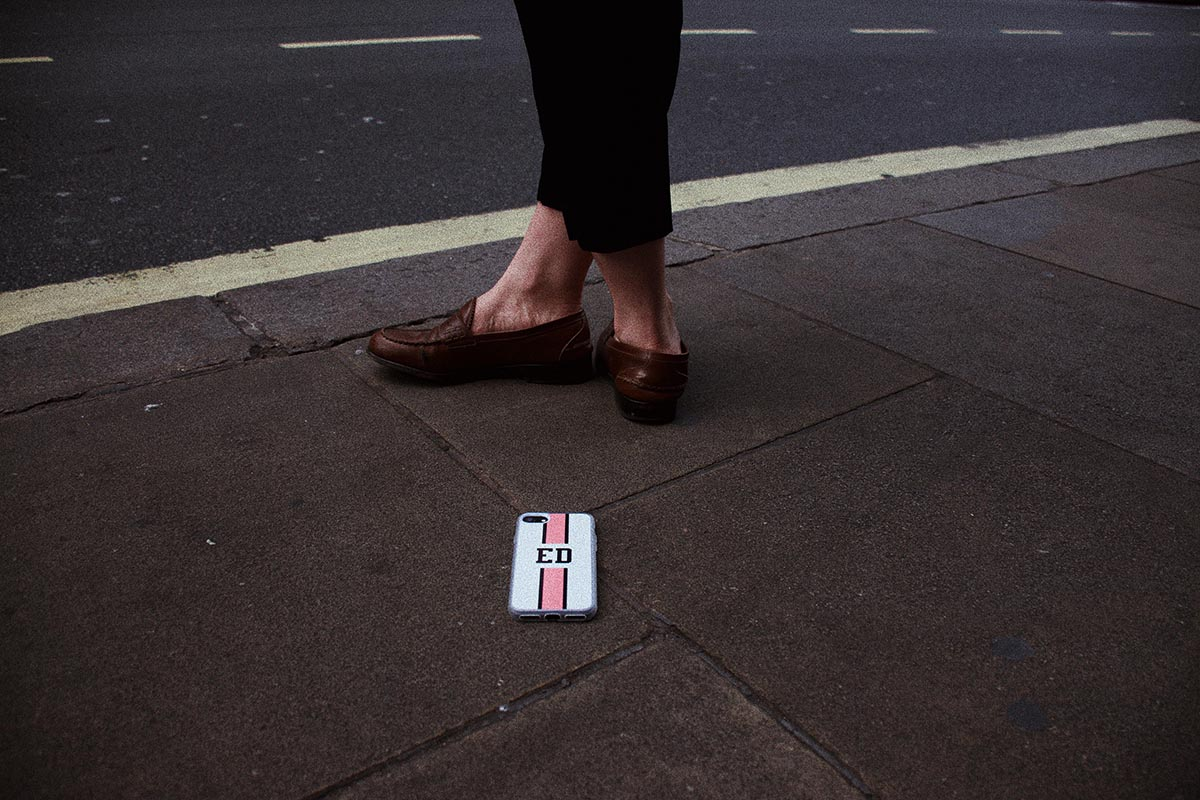 cover per iPhone con iniziali e linea centrale rosa vicino ai piedi di una donna