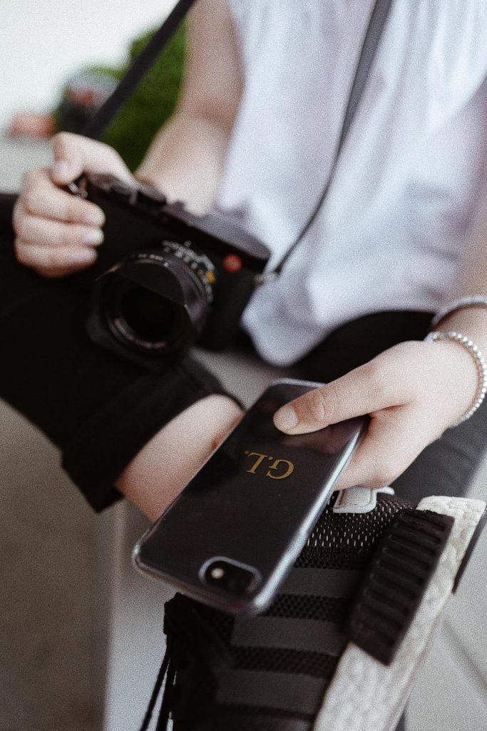 cover per iPhone con iniziali puntate color oro tenuta in mano da una ragazza con una fotocamera leica