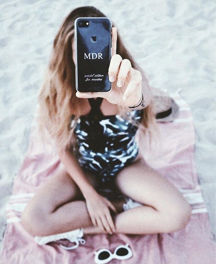 cover per iPhone con scritta special edition e iniziali in mano ad una ragazza in spiaggia.